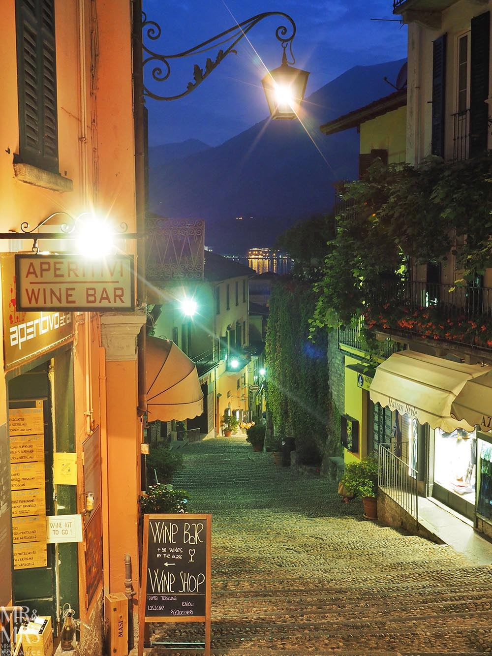 Ultimate Guide to Lake Como, Italy - Laneways of Bellagio with a sign for aperitivi and a wine bar. Steps lead down towards the lake