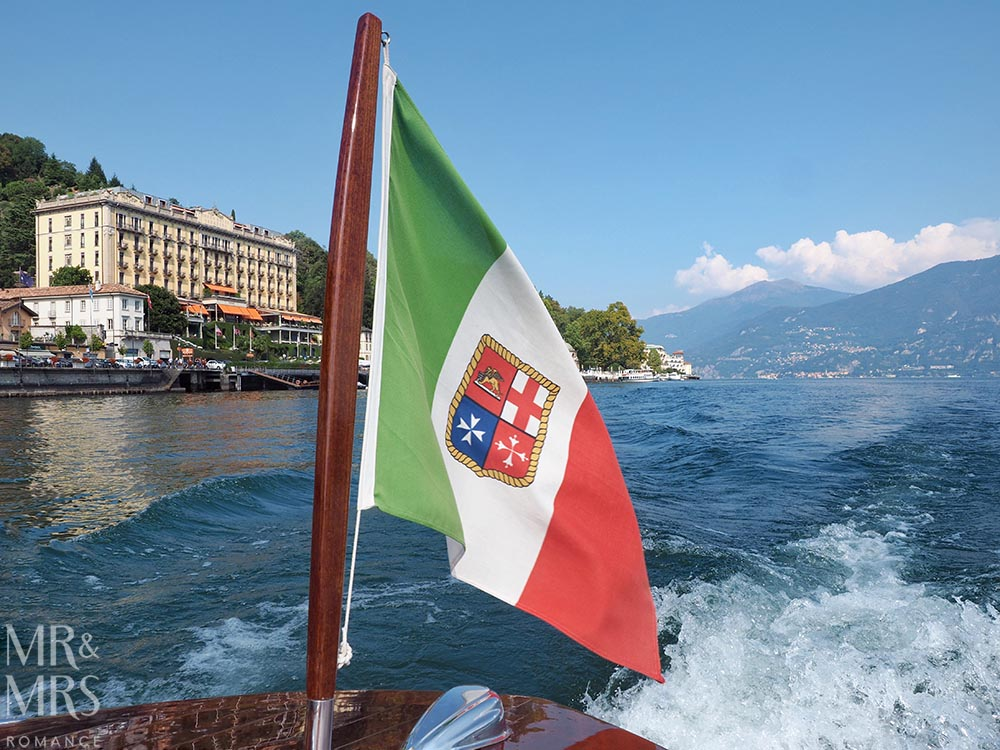 Ultimate Guide to Lake Como, Italy - Lake Como flag from the deck of a 1950s Venetian speedboat. Lake Como and the Grand Hotel Tremezzo in the background